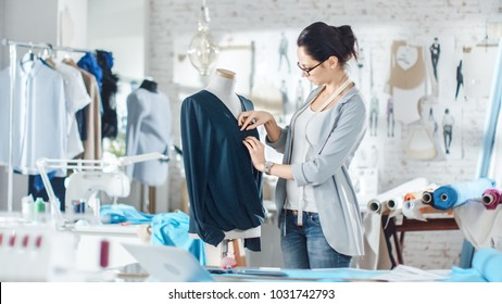 Beautiful Woman fashion, designer,  Working with Tailoring Mannequin, Adjusting Blouse. Her Studio is Bright and Sunny, Mannequins Standing around, Clothes Hanging, Colorful Fabrics Lying on the Table