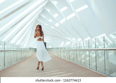 Beautiful woman fashion full body portrait on pedestrian bridge in Water Canal. Dubai.