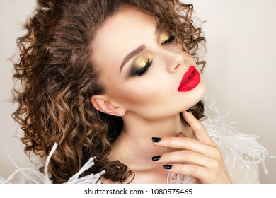 Beautiful woman with fashion make-up. Curly hair. Red lipstick.
