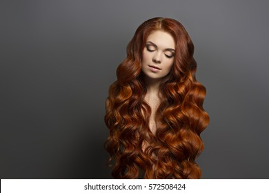 Beautiful woman fashion portrait with gorgeous long red hair and perfect makeup.