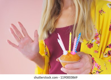 Beautiful woman in a fashionable dress is holding a small cake with festive colorful candles. Concept of a birthday or an anniversary. Candles show the number five