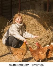 Beautiful woman feeding chikens