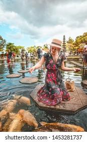 Beautiful woman feeding the fishes in Bali