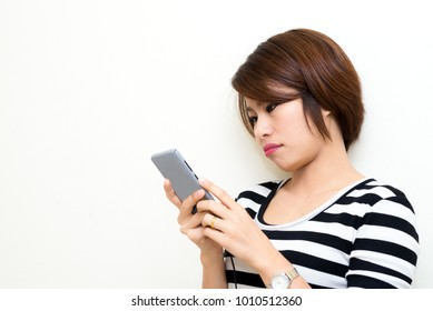 Beautiful woman feeling bored while using mobile phone in gray case, checking e-mail or waiting calling from some one on white background.