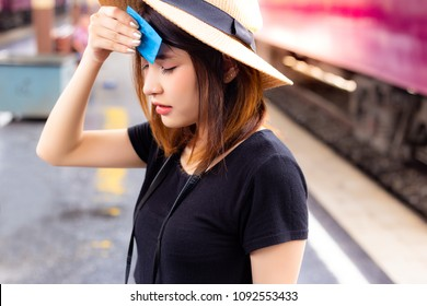 Beautiful woman feels so hot and tired in the summer season. Attractive beautiful girl uses facial tissue for sweating on her face. Charming beautiful woman is going to faint from the hot weather