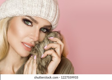 Beautiful woman, female model with in a warm winter jacket and hat. Model presents winter clothing.