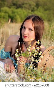 beautiful woman in a field of flowers chamomile with cowboy hat