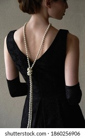Beautiful woman figure in profile in a black dress and pearls in the style of 20-30 years of the XX century     - Shutterstock ID 1860256906