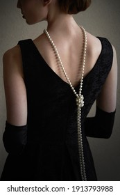 Beautiful woman figure in profile in a black dress and pearls in the style of 20-30 years of the XX century - Shutterstock ID 1913793988