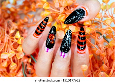 Beautiful woman Fingernail with Black and Orange color Gel Nail Art Design for Halloween Festival Painting Cobweb and shiny Crystal Spider on Ringfinger