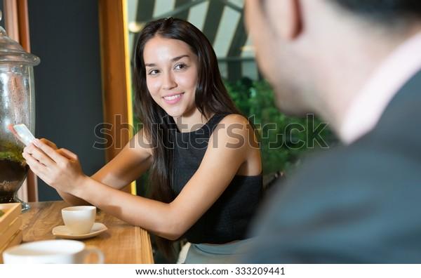 Beautiful woman flirting with businessman in coffee shop