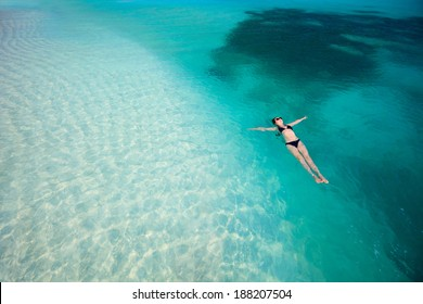 Beautiful woman floating in turquoise tropical water