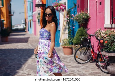 Beautiful woman in a floral dress walking on the street. Attractive young lady in sunglasses posing between bright colorful houses. Summer lifestyle photo of a girl in stylish lilac dress.