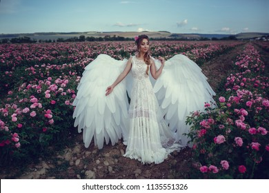 Beautiful woman in a floral park, garden roses. Makeup, hair, a wreath of roses. Long Wedding Dress. Woman in Boho style with wings