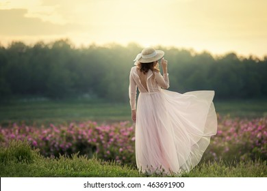 Beautiful woman in a floral park, garden roses. Makeup, hair, a wreath of roses. Long Wedding Dress
