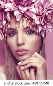 Beautiful woman with flower crown and makeup on pink background holding hand under her chin