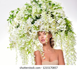 Beautiful woman with flowers in her hair. Bouquet of Beautiful Flowers. Hairstyle with flowers. Nature Hairstyle.