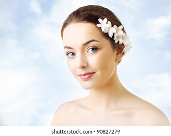 Beautiful woman with flowers in her hair and pure skin on background of sky