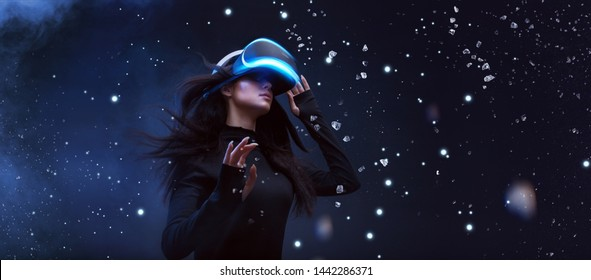 Beautiful woman with flowing hair in futuristic dress over dark background. Girl in glasses of virtual reality. Augmented reality, game, future technology concept. VR.