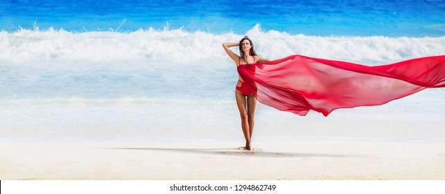 Beautiful Woman with Flying Fabric of Red Color on the Coast of the Ocean