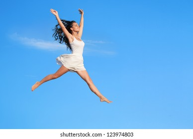 Beautiful woman flying in jump against blue sky