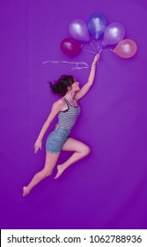 Beautiful woman is flying on balloons towards her dream on ultra violet background. She wears jeans shorts and striped t-shirt. With fluttering long brown hair. Multicolored balloons.