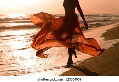 Beautiful woman with flying red dress, beach
