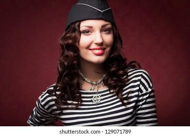 beautiful woman in forage-cap and frock smiling, studio shot