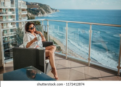 Beautiful woman of forty years drinking her morning coffee on the balcony. Weekend relaxation concept