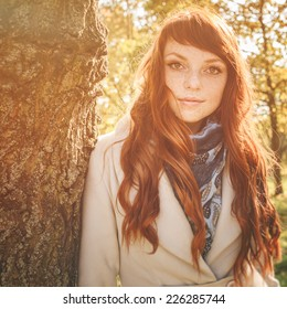 beautiful woman with freckle and red long hair in autumn park