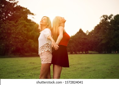Beautiful woman with friend playing or relaxing in a park in vacation day, portrait of caucasian girl or traveler posing