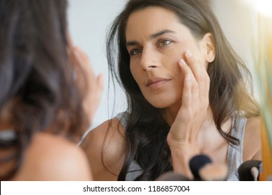 Beautiful woman in front of mirror looking at her face