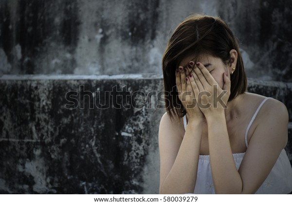 Beautiful woman in frustrated depression and crying. Conceptual of sadness and problems human in dark tone.