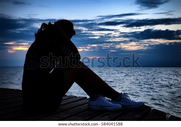 Beautiful woman in frustrated depression sitting on wooden bridge, near the beach on sunset. Concept of Major depressive disorder, unemployed, sadness, depressed and human problems in dark tone.