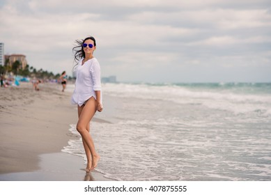 Beautiful woman full body portrait walking on Hollywood beach in Miami, florida. Filtered image.