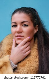 Beautiful woman in a fur coat against blue background