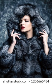 Beautiful woman in a fur coat with hood posing in studio. Luxury, rich lifestyle. Fashion shot.