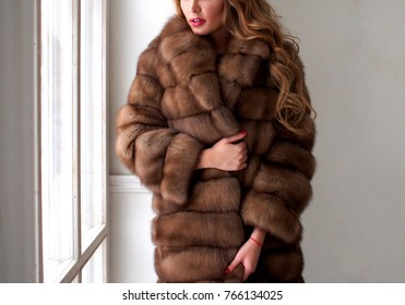 A beautiful woman in a fur coat standing by the window. Fashion and style.