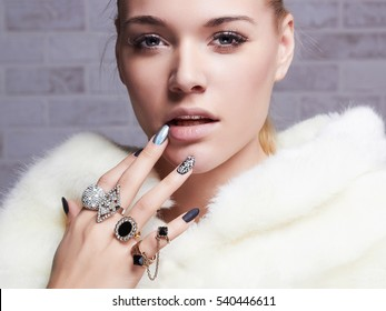 beautiful woman in fur, hands with jewelry.close-up beauty and fashion portrait. girl make-up and manicure
