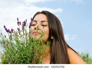 Beautiful woman in the garden smelling flowers. Girl smelling a bouquet of lavender  on a hot summer day.