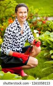 Beautiful woman gardener with shovel and flower in the flowerbed. Fashion and Style.