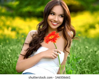 Beautiful Woman With Gerbera Flower Enjoying Nature against Nature Background