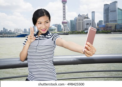 Beautiful woman gesturing peace sign while taking selfie through smart phone against Pudong skyline