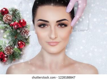 Eine schöne Frau bekommt eine Gesichtsmassage im Wellnessbereich. Nahaufnahme des Gesichts der Frau und Neujahrskranz mit Schneeflocken.
