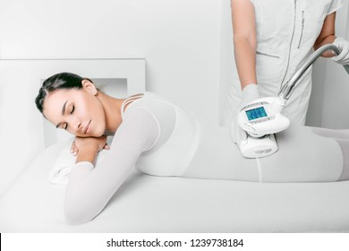 Beautiful woman getting beauty therapy against cellulite with LPG machine on her buttocks. LPG massage for lifting body