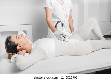 Beautiful woman getting beauty therapy against cellulite with LPG machine on her belly. LPG massage for lifting body and belly