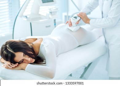 Beautiful woman getting beauty therapy against cellulite with LPG machine on her butt.