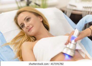 Beautiful woman getting cavitation treatment at beauty salon