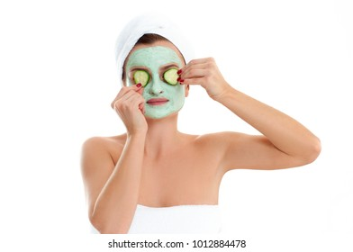 Beautiful woman is getting facial clay mask with cucumber on white background. Beauty, body care and spa concept