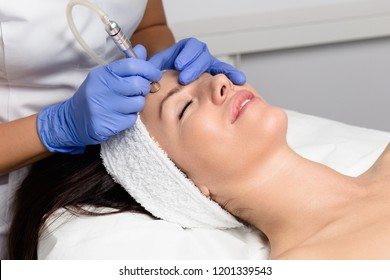Beautiful woman getting facial microdermabrasion peeling treatment at luxury cosmetic beauty spa clinic. Exfoliation, rejuvenation and hydratation. Cosmetology concept.